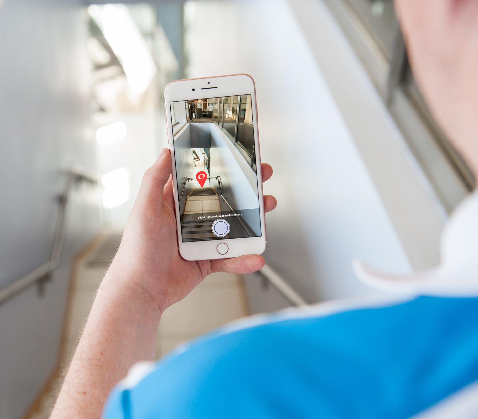 A user using the Clew application.  The picture shows a user standing at the top and an image on their smartphone directing them down the stairs.