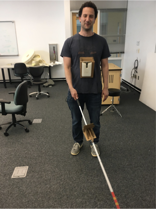 Paul Ruvolo demonstrating the use of our system for O&M training.  The picture shows Paul holding a long cane that has been instrumented with a special tracking tag.  He is also wearing a Google Tango smartphone around his neck using a custom harness that we have created.